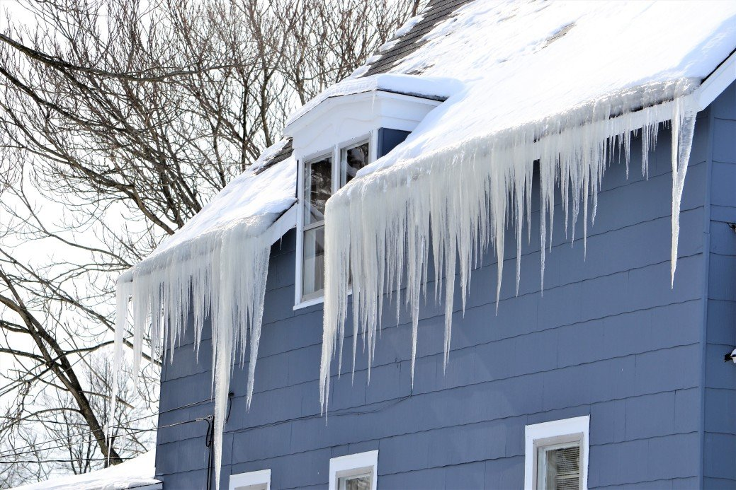 a blue house has icicles several feet long hanging from it